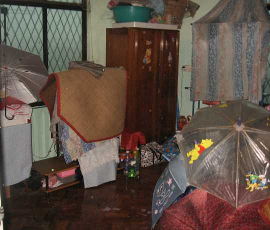 Covering with umbrellas in the bed room during Cyclone Nargis, Yangon, Myanmar
